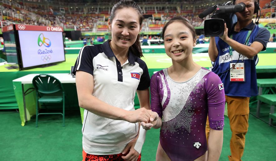 """FILE - In this Aug 7, 2016, file photo, South Korean gymnast Lee Eun-ju, right, and her North Korean counterpart Hong Un Jong shake hands and smile together for photographers during the artistic gymnastics women's qualification at the 2016 Summer Olympics in Rio de Janeiro, Brazil. The photo captured global headlines, and International Olympic Committee President Thomas Bach describes it as a """"great gesture."""" (Kim Do-hoon/Yonhap via AP, File)"""