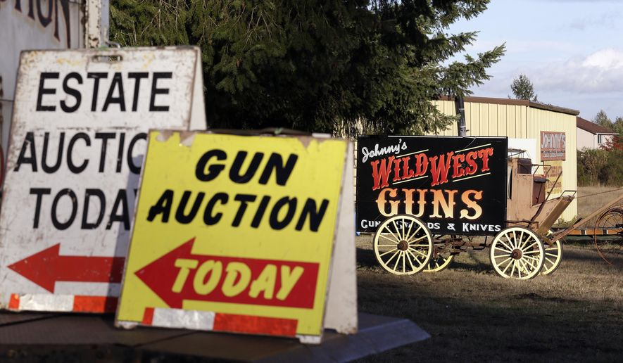 In this Oct. 20, 2017 photo, signs announce auctions for both guns and an estate at Johnny's Auction House, where the company handles gun sales for about a half dozen police departments and the Lewis County Sheriff's Office, in Rochester, Wash. Law enforcement officials around the U.S. are split over the longtime practice among police departments of selling the guns they confiscate. (AP Photo/Elaine Thompson)