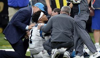 Carolina Panthers quarterback Cam Newton (1) is tended to by medical personnel after being sacked in the second half of an NFL football game against the New Orleans Saints in New Orleans, Sunday, Jan. 7, 2018. (AP Photo/Bill Feig)