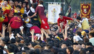 Filipino Roman Catholic devotees jostle to get closer and kiss the image of the Black Nazarene in a raucous procession to celebrate its feast day Tuesday, Jan. 9, 2017 in Manila, Philippines. A massive crowd of mostly barefoot Filipino Catholics joined the annual procession of a centuries-old statue of Jesus Christ under tight security. (AP Photo/Bullit Marquez)