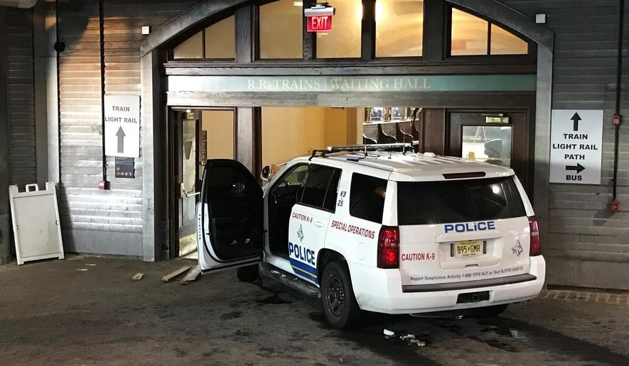 A police K-9 SUV sits on the scene after a person crashed it into the doors of the waiting room at the Hoboken, N.J., rail terminal Monday, Jan. 8, 2018. (Dan Strzelec via AP)