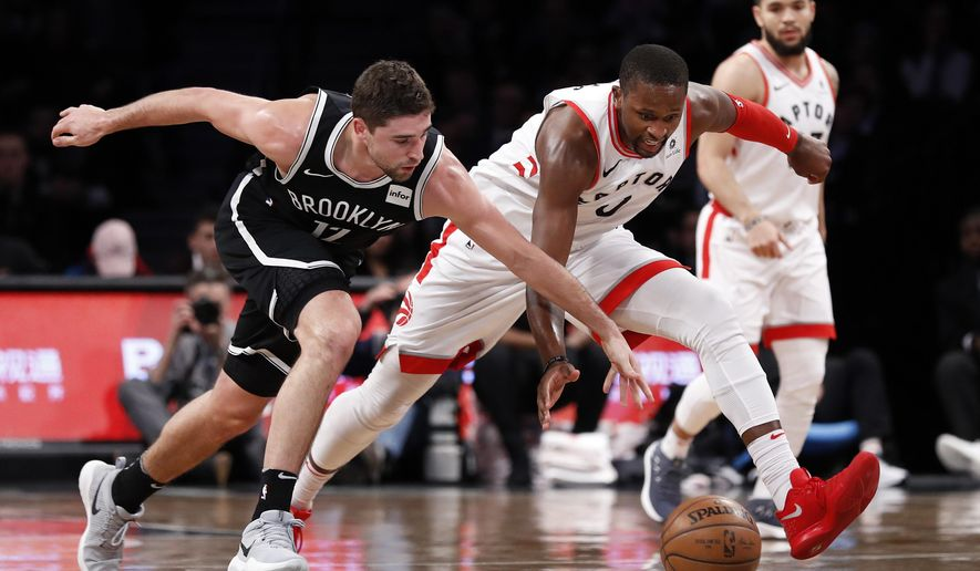 Brooklyn Nets' Joe Harris (12) battles for the ball with Toronto Raptors' CJ Miles (0) during the first half of an NBA basketball game Monday, Jan. 8, 2018, in New York. (AP Photo/Adam Hunger)