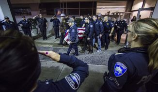 Officers and medical staff take part in a procession for officer Daniel McCartney, of Yelm, at St. Joseph Medical Center in Tacoma, Wash., on Monday, Jan. 8, 2018. The department said McCartney was responding to a home invasion in the Frederickson area, late Sunday night when he was shot during a foot chase. (Joshua Bessex/The News Tribune via AP)