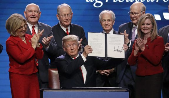 In this file photo, President Donald Trump holds up an executive order after signing it at the American Farm Bureau Federation annual convention Monday, Jan. 8, 2018, in Nashville, Tenn., as, from left, Rep. Diane Black, R-Tenn., Agriculture Secretary Sonny Perdue, Sen. Lamar Alexander, R-Tenn., Sen. Bob Corker, R-Tenn., Sen. Pat Roberts, R-Kan., and Rep. Marsha Blackburn, R-Tenn., applaud. Mrs. Blackburn, who is running for the U.S. Senate, will welcome Mr. Trump at a Nashville campaign rally on May 29, 2018. (AP Photo/Mark Humphrey) **FILE**
