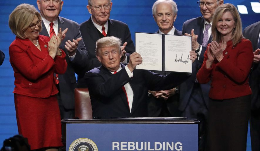 President Donald Trump holds up an executive order after signing it at the American Farm Bureau Federation annual convention Monday, Jan. 8, 2018, in Nashville, Tenn., as, from left, Rep. Diane Black, R-Tenn., Agriculture Secretary Sonny Perdue, Sen. Lamar Alexander, R-Tenn., Sen. Bob Corker, R-Tenn., Sen. Pat Roberts, R-Kan., and Rep. Marsha Blackburn, R-Tenn., applaud (AP Photo/Mark Humphrey)
