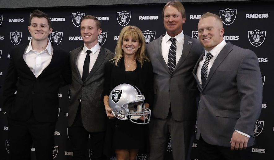 Oakland Raiders head coach Jon Gruden, second from right, poses for photographs with his family after an NFL football press conference Tuesday, Jan. 9, 2018, in Alameda, Calif. (AP Photo/Marcio Jose Sanchez)