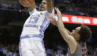 North Carolina's Cameron Johnson (13) dunks against Boston College's Jordan Chatman (25) during the first half of an NCAA college basketball game in Chapel Hill, N.C., Tuesday, Jan. 9, 2018. (AP Photo/Gerry Broome)