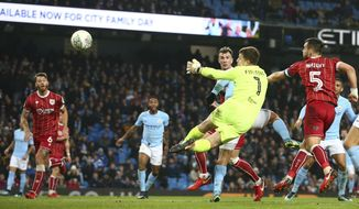 Bristol City's goalkeeper Frank Fielding watches as a ball from Manchester City's Sergio Aguero heads towards the goal during the English League Cup semifinal first leg soccer match between Manchester City and Bristol City at the Etihad stadium in Manchester, England, Tuesday, Jan. 9, 2018. (AP Photo/Dave Thompson)