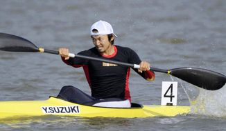 In this November 2010, photo, Japan's Yasuhiro Suzuki competes in the mens single kayak race at the 16th Asian Games in Shanwei, China. The top Japanese canoe sprinter has been banned for eight years, disqualifying him from the Tokyo Olympics, for lacing his rival's drink with a prohibited drug which caused him to fail a doping test. The Japan Anti-Doping Agency said Tuesday, Jan. 9, 2018 that Suzuki was banned for putting an anabolic steroid into the drink bottle of his rival at a national championship in September. (Kyodo News via AP)