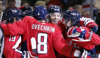 Washington Capitals defenseman John Carlson, facing camera, celebrates his goal with his teammates, including left wing Alex Ovechkin (8), from Russia, during the first period of an NHL hockey game against the Vancouver Canucks, Tuesday, Jan. 9, 2018, in Washington. (AP Photo/Alex Brandon)