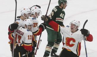 Minnesota Wild's Jared Spurgeon, top center, skates away as Calgary Flames' Dougie Hamilton (27) is congratulated on his winning goal in overtime of an NHL hockey game Tuesday, Jan. 9, 2018, in St. Paul, Minn. The Flames won 3-2. Spurgeon scored the game-tying goal in the third period for the Wild. (AP Photo/Jim Mone)