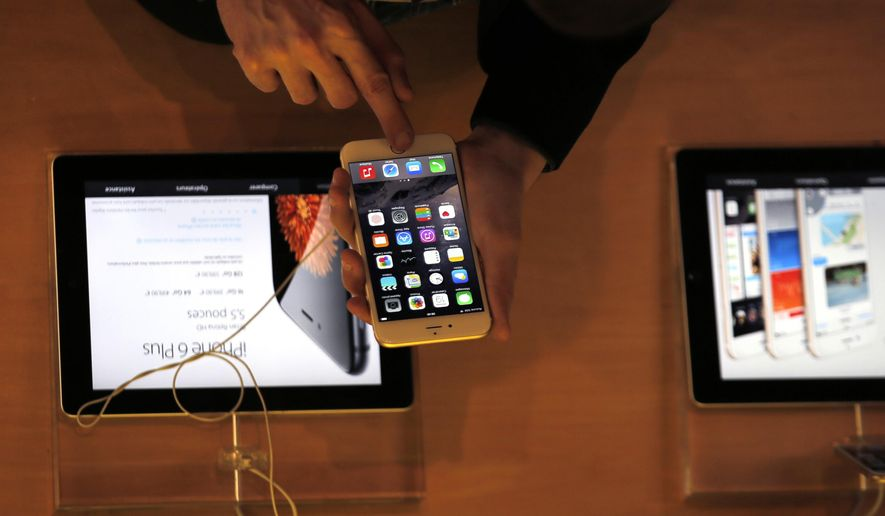In this Sept. 19, 2014, file photo, a customer checks the iPhone 6, in Paris. A French prosecutor office said Tuesday, Jan.9, 2018, that an investigation into Apple over alleged planned obsolescence of some of its smartphones has been opened. It follows a legal complaint filed in December by pro-consumer group Halte a l'obsolescence programmee (Stop Planned Obsolescence). Under a 2015 law, it is banned to intentionally shorten lifespan of a product in order to incite customers replace it. (AP Photo/Christophe Ena, File)