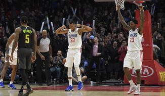 Los Angeles Clippers forward Wesley Johnson, center, and guard Lou Williams, right, celebrate while Atlanta Hawks guard Malcolm Delaney walks off as they win 108-107 in a basketball game, Monday, Jan. 8, 2018, in Los Angeles. (AP Photo/Mark J. Terrill)