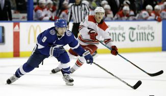 Tampa Bay Lightning center Tyler Johnson (9) beats Carolina Hurricanes right wing Sebastian Aho, of Finland, to the puck during the second period of an NHL hockey game Tuesday, Jan. 9, 2018, in Tampa, Fla. (AP Photo/Chris O'Meara)