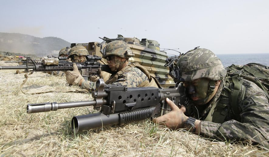 In this March 30, 2015, file photo, a South Korean Marine, right and U.S. Marines aim their weapon near amphibious assault vehicles during the U.S.-South Korea joint landing military exercises as a part of the annual joint military exercise Foal Eagle between South Korea and the United States in Pohang, South Korea. (AP Photo/Lee Jin-man, File)