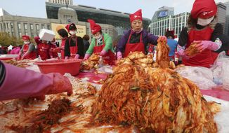 FILE - In this Nov, 3. 2017, file photo, women make kimchi, a traditional fermented South Korean pungent vegetable dish, to donate to needy neighbors in preparation for the winter season during Kimchi Festival at Seoul City Hall Plaza in Seoul, South Korea. Spicy, pungent kimchi; thick fermented soups filled with meat so tender it falls off the bone; barbecued everything; all of it washed down with ubiquitous soju liquor. (AP Photo/Ahn Young-joon, File)