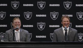 Oakland Raiders new head coach Jon Gruden, right, smiles as he listens to a question from former Raiders player Charles Woodson, as he sits next to owner Mark Davis during an NFL football press conference Tuesday, Jan. 9, 2018, in Alameda, Calif. (AP Photo/Marcio Jose Sanchez)