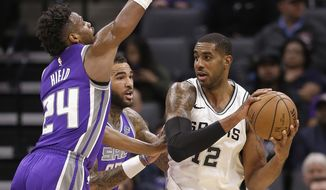 Sacramento Kings' Buddy Hield, left, and Willie Cauley-Stein, center, pressure San Antonio Spurs forward LaMarcus Aldridge during the first quarter of an NBA basketball game Monday, Jan. 8, 2018, in Sacramento, Calif. (AP Photo/Rich Pedroncelli)
