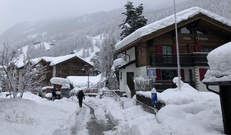In this image  provided by Paul Black a man walks in the  snow in Zermatt Switzerland Tuesday Jan. 9, 2018. Swiss authorities near the famed Matterhorn peak have closed ski slopes, hiking trails, cable cars, roads and train service into the nearby town of Zermatt amid a heightened risk of avalanches, stranding some 13,000 tourists in the town. (Paul Black via AP)