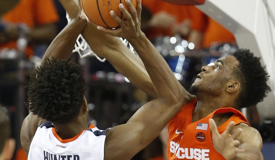 Virginia guard De'Andre Hunter (12) shoots as Syracuse forward Oshae Brissett (11) defends during the first half of an NCAA college basketball game in Charlottesville, Va., Tuesday, Jan. 9, 2018. (AP Photo/Steve Helber)