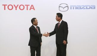 FILE- In this Aug. 4, 2017, file photo, Toyota Motor Corp. President Akio Toyoda, left, and Mazda Motor Corp. President Masamichi Kogai shake hands after a press conference in Tokyo. Japanese automakers Toyota and Mazda have picked Alabama as the site of a new $1.6 billion joint-venture auto manufacturing plant, a person briefed on the decision said Tuesday, Jan. 9, 2018. (AP Photo/Eugene Hoshiko, File)