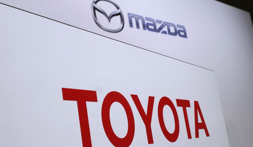 FILE- In this Aug. 4, 2017, file photo, logos of Toyota Motor Corp., bottom, and Mazda Motor Corp., top, are placed prior to a news conference in Tokyo. Japanese automakers Toyota and Mazda have picked Alabama as the site of a new $1.6 billion joint-venture auto manufacturing plant, a person briefed on the decision said Tuesday, Jan. 9, 2018. (AP Photo/Eugene Hoshiko, File)
