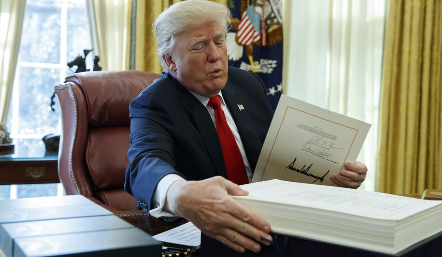 President Donald Trump grabs a box containing the tax bill after signing it in the Oval Office of the White House, Friday, Dec. 22, 2017, in Washington. (AP Photo/Evan Vucci)