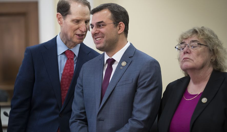 Sen. Ron Wyden, D-Ore., left, a member of the Senate Intelligence Committee, confers with Rep. Justin Amash, R-Mich., as they hold a news conference with a bipartisan group of House and Senate lawmakers, including Rep. Zoe Lofgren, D-Calif., right, who are demanding the U.S. government should be required to seek warrants if it wants to search for information about Americans and insist on reforms to the FISA Amendments Reauthorization Act of 2017 to protect Americans' rights, at the Capitol in Washington, Wednesday, Jan. 10, 2018. (AP Photo/J. Scott Applewhite)