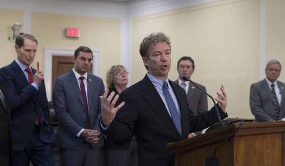 Sen. Rand Paul, R-Ky., center, takes a reporter's question as he joins a bipartisan group of House and Senate lawmakers who are demanding the U.S. government should be required to seek warrants if it wants to search for information about Americans and insist on reforms to the FISA Amendments Reauthorization Act of 2017 to protect Americans' rights, at the Capitol in Washington, Wednesday, Jan. 10, 2018. From left are, Sen. Ron Wyden, D-Ore., Rep. Justin Amash, R-Mich., Rep. Zoe Lofgren, D-Calif., Rep. Thomas Massie, R-Ky., and Rep. Ralph Norman, R-S.C. (AP Photo/J. Scott Applewhite)