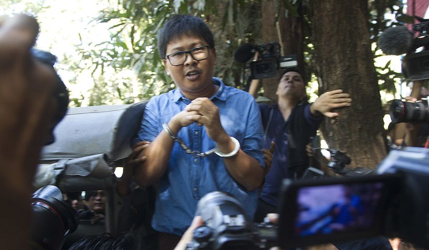 Reuters journalist Wa Lone speaks to media cuffed from the back of a police truck as he leaves court Wednesday, Jan.10, 2018, outside of Yangon, Myanmar. (AP Photo/Thein Zaw)