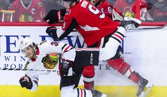 Chicago Blackhawks' Ryan Hartman (38) gets pushed to the ice by Ottawa Senators' Bobby Ryan during the first period of an NHL hockey game, Tuesday, Jan. 9, 2018, in Ottawa, Ontario. (Sean Kilpatrick/The Canadian Press via AP)