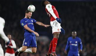 Chelsea's Danny Drinkwater jumps for the ball with Arsenal's Danny Welbeck, right, during the English League Cup semifinal, first leg, soccer match between Chelsea and Arsenal at Stamford Bridge stadium in London, Wednesday, Jan. 10, 2018. (AP Photo/Kirsty Wigglesworth)