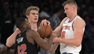 New York Knicks forward Kristaps Porzingis (6) fights for the ball with Chicago Bulls guard Kris Dunn (32) during the first quarter of an NBA basketball game Wednesday, Jan. 10, 2018, at Madison Square Garden in New York. (AP Photo/Bill Kostroun)