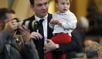 Colorado State Rep. Alec Garnet, D-Denver, left, holds his 2-year-old son, Ashton, as the Colorado House of Representatives convenes for the start of the 2018 session Wednesday, Jan. 10, 2018, in the State Capitol in Denver. Lawmakers are facing the tasks of funding for roads and schools as well as trying to shore up the state's pension fund during the session, which runs through early May. (AP Photo/David Zalubowski)
