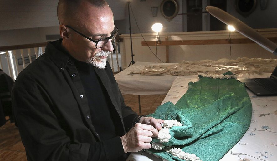 In this Jan. 2, 2018, photo, Jeff Stolz, a professor in the Viterbo University Theater Department, works conserving a dress from the 1970's at the La Crosse County Historical Society in La Crosse, Wis. The dress will be featured in an upcoming exhibit featuring the clothing of prominent La Crosse women. (Erik Daily/La Crosse Tribune via AP)