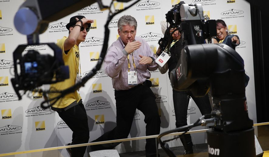 Kirk Clyatt, center, dances for remote cameras at the Nikon booth during CES International, Tuesday, Jan. 9, 2018, in Las Vegas. (AP Photo/John Locher)
