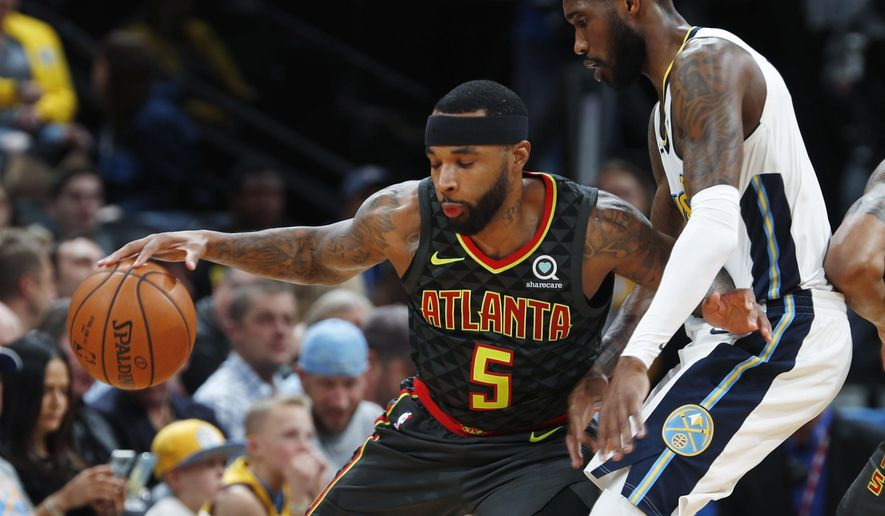 Atlanta Hawks guard Malcolm Delaney, left, works the ball inside as Denver Nuggets guard Will Barton defends in the first half of an NBA basketball game Wednesday, Jan. 10, 2018 in Denver. (AP Photo/David Zalubowski)