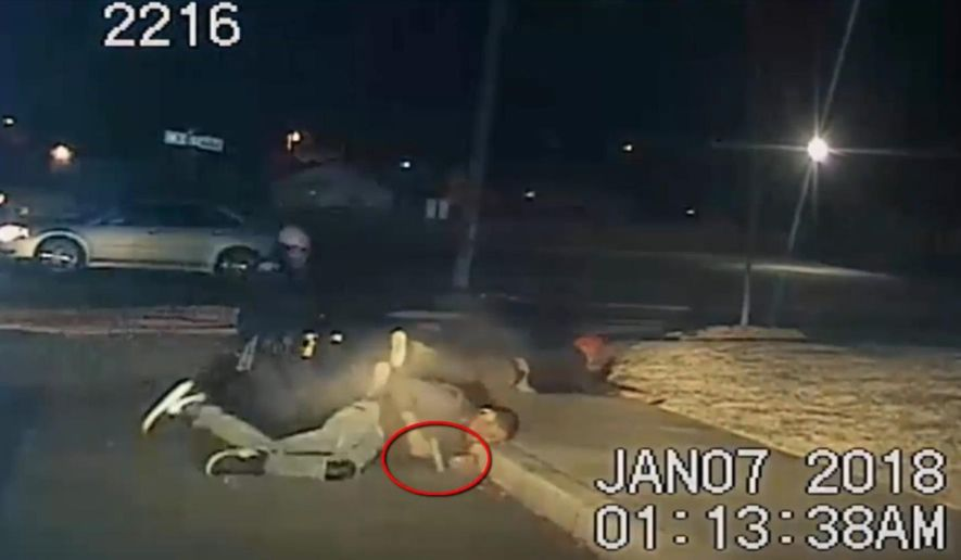 This Sunday, Jan. 7, 2018, frame grab from a police cam video provided by the North Little Rock Police Department shows a confrontation between police and Charles Smith, foreground, in North Little Rock, Ark. Smith, holding a gun, rolls away from an officer after being shot by police during a traffic stop. The tape shows officers wrestling Smith to the ground during a pat-down search and Smith reaching for and firing a handgun. The man in the background at right was removed from the same vehicle as Smith. The red circle was added by the source. (North Little Rock Police via AP)