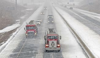 Traffic on Interstate 94 moves as snow began accumulating on the east-west highway in this view of eastbound vehicles crossing the Missouri River at Bismarck, N.D., Wednesday, Jan. 10, 2018. (Tom Stromme/The Bismarck Tribune via AP)