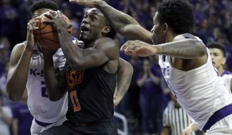 Oklahoma State guard Brandon Averette (0) splits Kansas State defenders James Love III, left, and Amaad Wainright, right, during the first half of an NCAA college basketball game in Manhattan, Kan., Wednesday, Jan. 10, 2018. (AP Photo/Orlin Wagner)