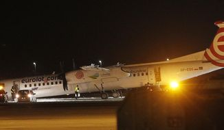 A Polish LOT airline passenger plane rests with its nose down on the runway after making an emergency landing with 59 passengers and four crew aboard, at the international Chopin Airport in Warsaw, Poland, Wednesday, Jan. 10, 2018.  Authorities think the front wheel malfunctioned during landing, but nobody was injured in the incident.(AP Photo/Czarek Sokolowski)