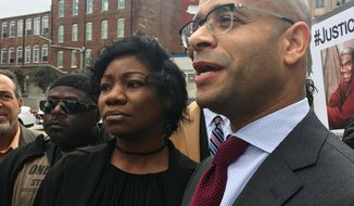 Monteria Robinson, mother of Jamarion Robinson, who was schizophrenic and shot by police in August 2016, stands with her lawyer, Andrew M. Stroth, as he addresses reporters at a news conference outside the federal courthouse, Wednesday, Jan. 10, 2018, in Atlanta. A federal civil rights lawsuit alleges law enforcement officers used excessive force and then tried to cover their actions in the fatal shooting of Jamarion Robinson.  (AP Photo/Kate Brumback)