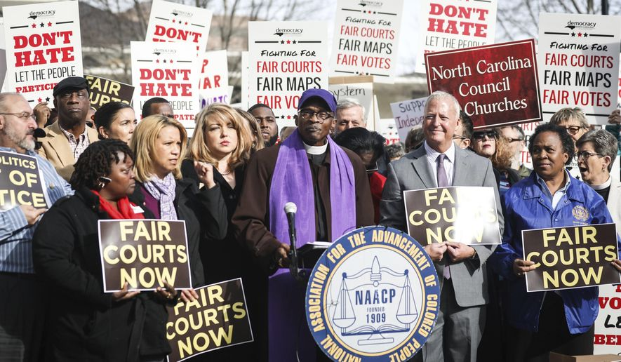 """North Carolina NAACP President, the Rev. Dr. T. Anthony Spearman, speaks to a large crowd Wednesday, Jan. 10, 2018, about a federal court's decision on Tuesday to strike down North Carolina's congressional map in Raleigh, N.C. Tuesday's """"decision is a mammoth decision,"""" said Spearman. (Julia Wall/The News & Observer via AP)"""