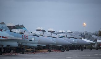 In this file photo taken on Friday, March 4, 2016, Russian Su-27 fighter jets and Su-34 bomber, right in the back, are parked at Hemeimeem air base in Syria. (AP Photo/Pavel Golovkin, File) **FILE**