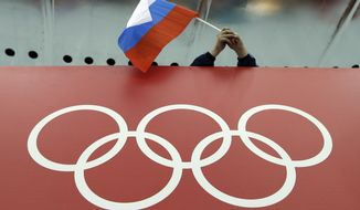 FILE - In this Feb. 18, 2014 file photo, a Russian skating fan holds the country's national flag over the Olympic rings at Adler Arena Skating Center during the 2014 Winter Olympics in Sochi, Russia. The Court of Arbitration for Sport has received 20 more appeals from Russian athletes against Olympic doping bans, taking the total to 42. The athletes' appeals will be fast-tracked. CAS said those cases will be heard together in the week beginning Jan. 22, and it expects verdicts will be issued by Jan. 31. (AP Photo/David J. Phillip, File)