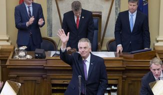 Virginia Gov. Terry McAuliffe waves to the gallery as he addresses a joint session of the the 2018 session in the House chambers at the Capitol in Richmond, Va., Wednesday, Jan. 10, 2018. Gov.-elect Lt. gov. Ralph Northam, top left, House speaker Kirk Cox, R-Colonial Heights, top center, and State Sen. Stephen Newman, R-Bedford, right, listen. (AP Photo/Steve Helber)