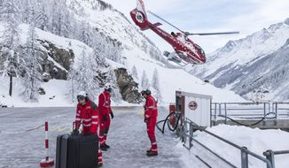 Support staff handle baggage of tourists at the heliport of Air Zermatt for an airlift into the valley to Raron, in Zermatt, Wednesday Jan. 10, 2018. Due to heavy snowfall and rain showers, Zermatt can only be reached by air. Swiss authorities have closed roads and train service into the town of Zermatt amid a heightened risk of avalanches, stranding some 13,000 tourists in the town. (Dominic Steinmann/Keystone via AP)