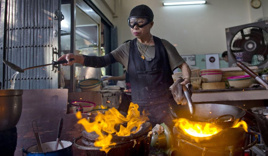 "In this Dec. 20, 2017, photo, Thai cook Supinya Jansuta, 72, better known as ""Jay Fai,"" wearing goggles, cooks with two flaming woks at her eatery in Bangkok, Thailand. After spending more than three decades cooking in an unassuming outdoor kitchen, Jay Fay has been propelled to international culinary stardom by having her restaurant awarded a Michelin star.(AP Photo/Gemunu Amarasinghe)"