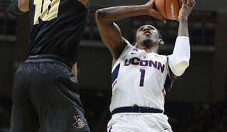 Connecticut's Christian Vital, right, shoots as Central Florida's Dayon Griffin, left, defends during the first half of an NCAA college basketball game, Wednesday, Jan. 10, 2018, in Storrs, Conn. (AP Photo/Jessica Hill)