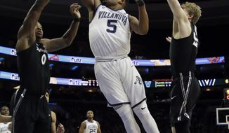 Villanova's Phil Booth, center, goes up for a shot between Xavier's Tyrique Jones, left, and J.P. Macura during the first half of an NCAA college basketball game, Wednesday, Jan. 10, 2018, in Philadelphia. (AP Photo/Matt Slocum)